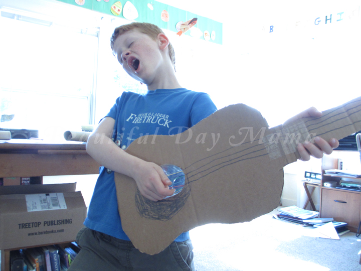 Young Son rocking out with his cardboard guitar