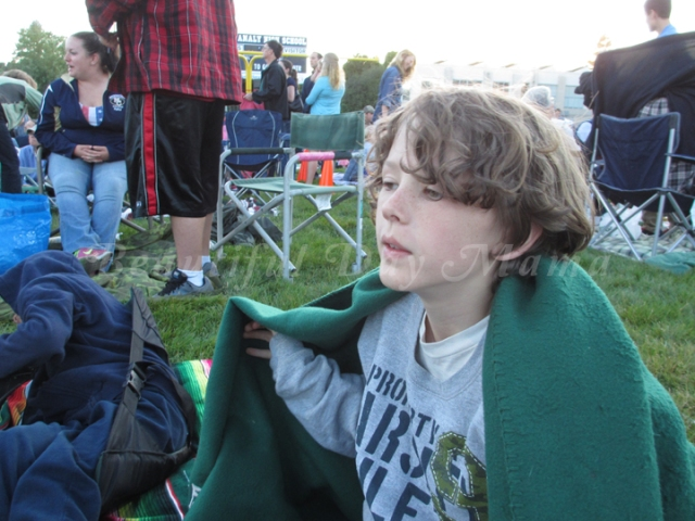 Brother with a blanket wrapped around him as the evening cools down